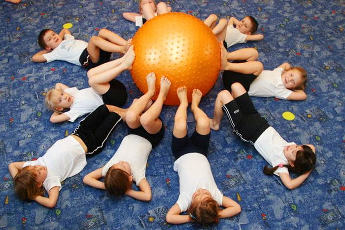Дети выполняют упражнение с фитболом