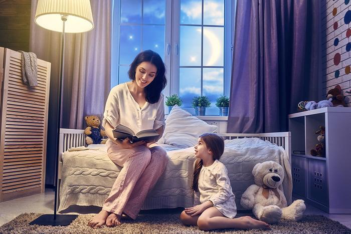 Мама читает дочке сказки на ночь