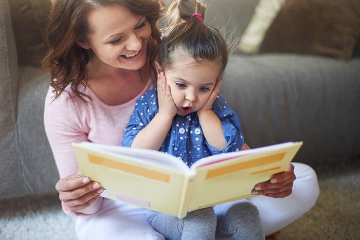 Маленькая девочка смотрит иллюстрации в книжке