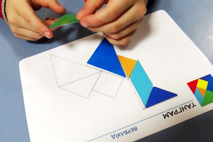 Ребенок складывает фигуру из деталей танграма