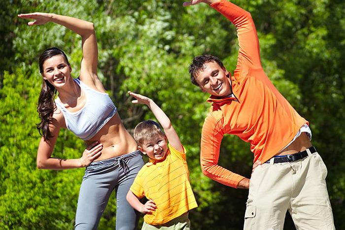 Семья делает зарядку на свежем воздухе