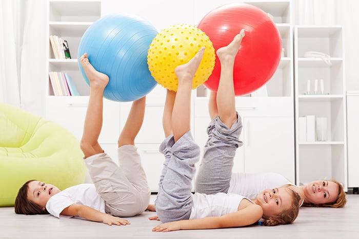 Дети с мамой занимаются гимнастикой с фитболами