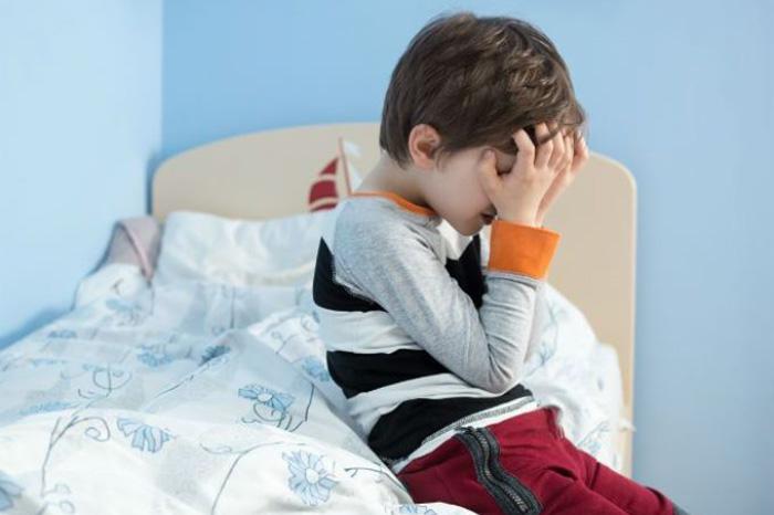 Ребенок плачет, сидя на кровати