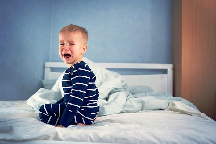 Ребенок плачет в кровати