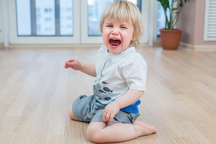Ребенок плачет, сидя на полу