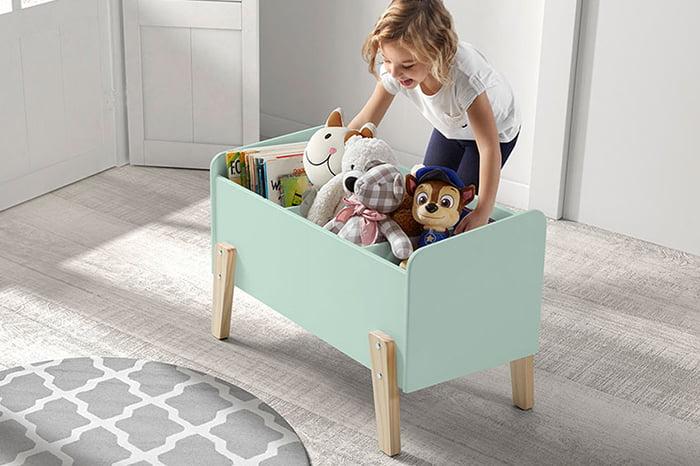 Девочка складывает игрушки в ящик