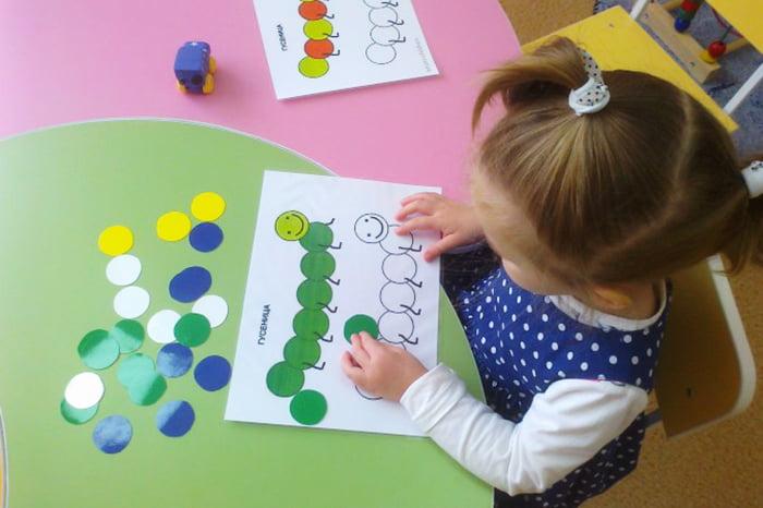 Девочка собирает гусеницу из цветных кружочков