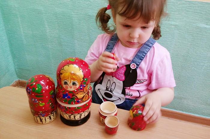 Девочка играет с матрешкой