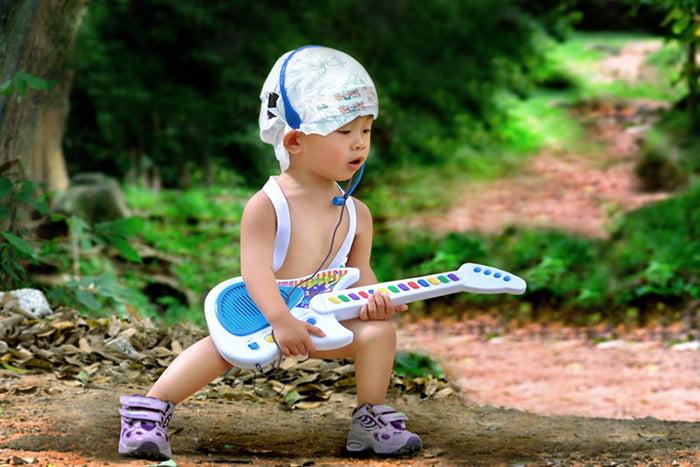 Ребенок с игрушечной гитарой