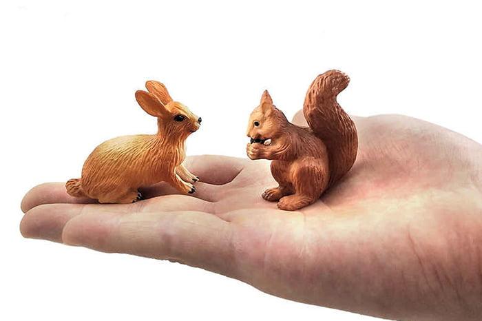 Фигурки зайца и белочки на ладони