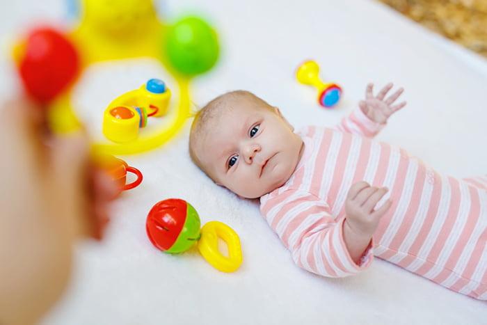 Новорожденный малыш смотрит на погремушку
