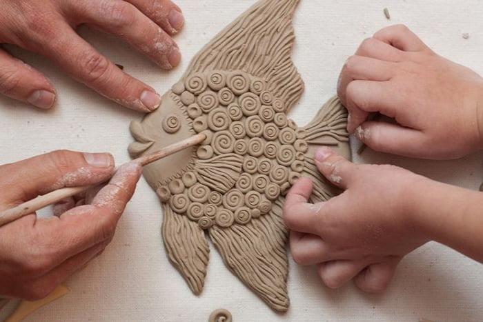 Взрослый и ребенок лепят рыбку из глины
