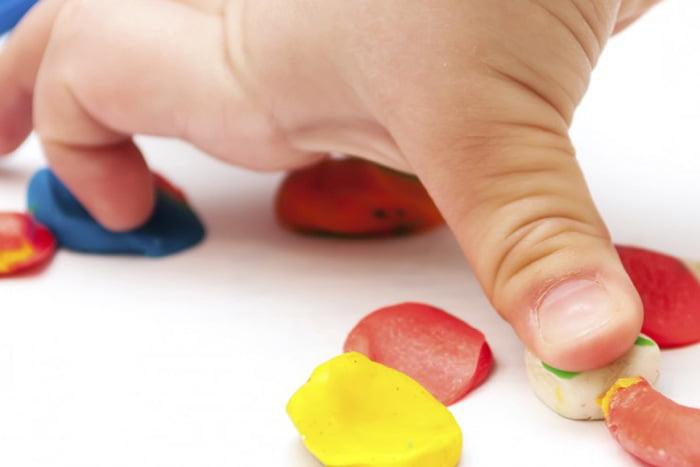 Ребенок лепит пластилин на бумагу
