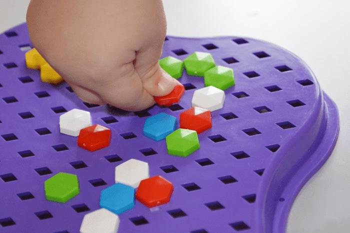 Ребенок собирает детали мозаики
