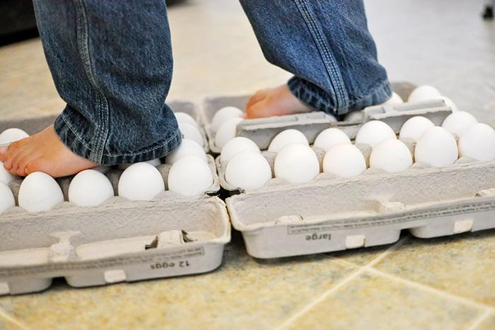 Ребенок ходит по лоткам с куриными яйцами