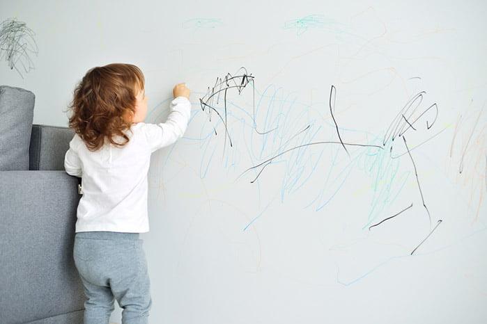 Маленькая девочка рисует на стене