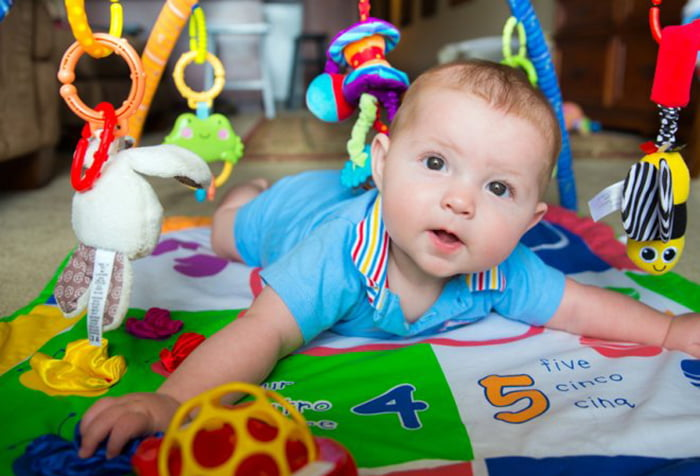Ребенок на красочном развивающем коврике