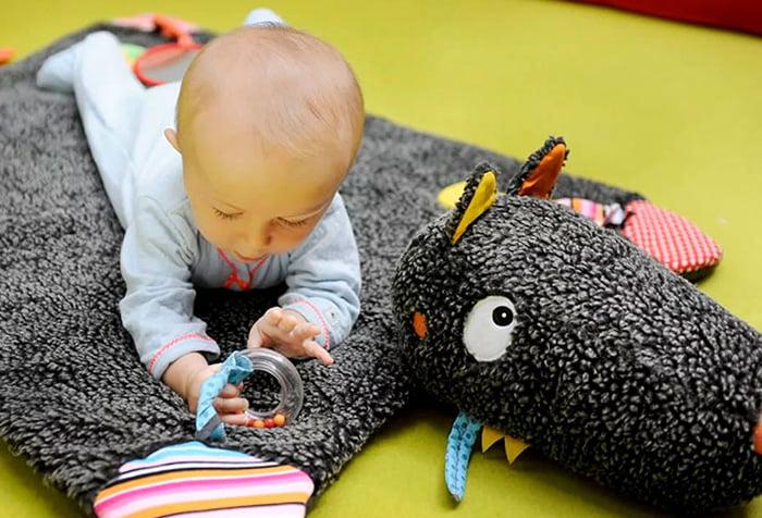 Малыш играет на развивающем коврике