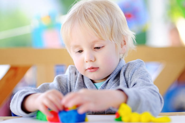 Трехлетний ребенок лепит из пластилина