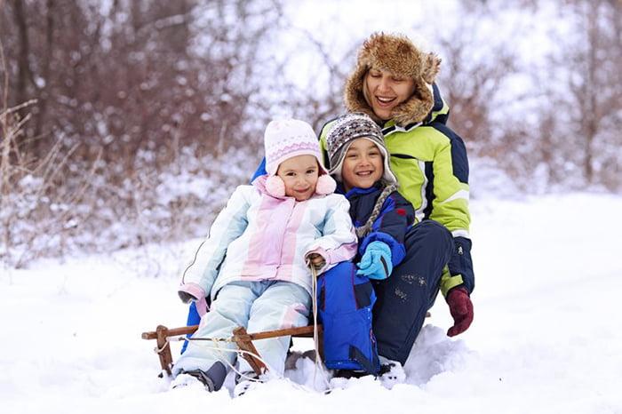 Женщина с детьми катается на санках