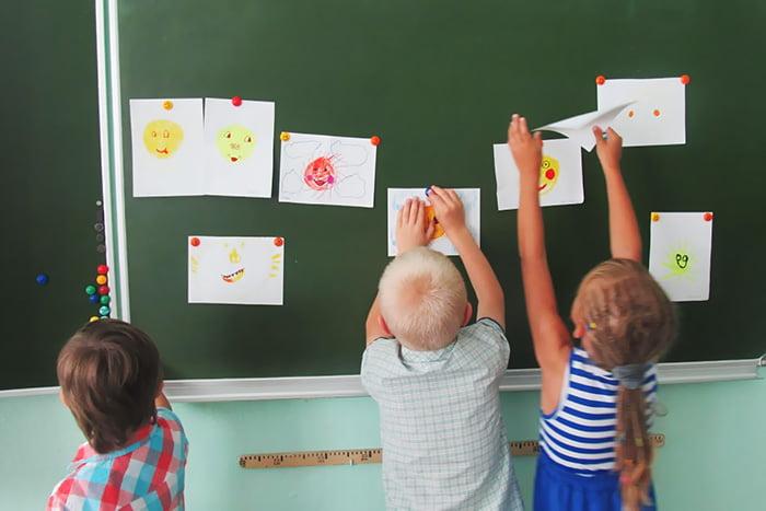 Дети вешают рисунки на доску