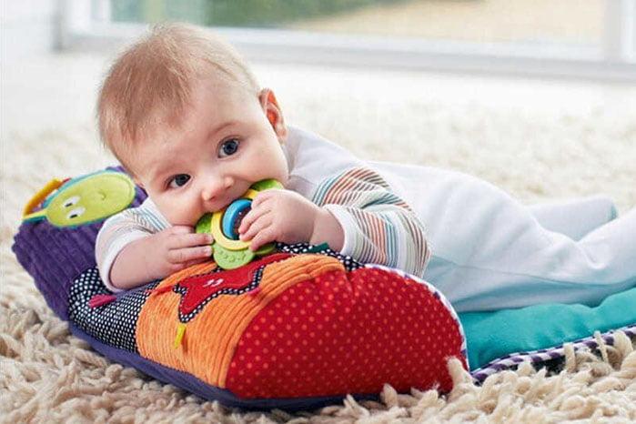 Новорожденный грызет погремушку