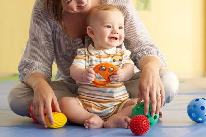 Мама играет с полугодовалым малышом