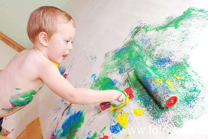 Ребенок рисует на стене валиком