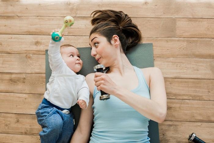 Мама с малышом на гимнастическом коврике