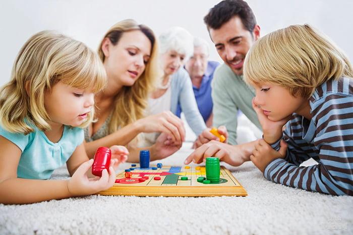 Семья играет в детскую настольную игру