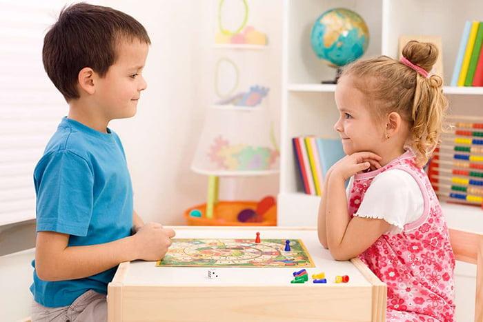 Мальчик и девочка за настольной игрой