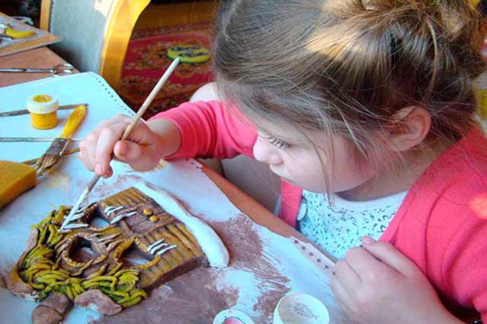 Девочка красит поделку из соленого теста