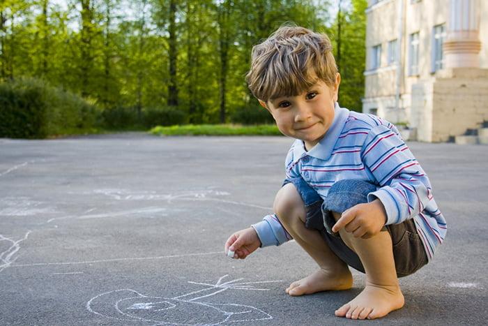 Четырехлетний мальчик рисует на асфальте