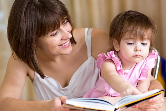 Маленькая девочка рассматривает книжку на руках у мамы