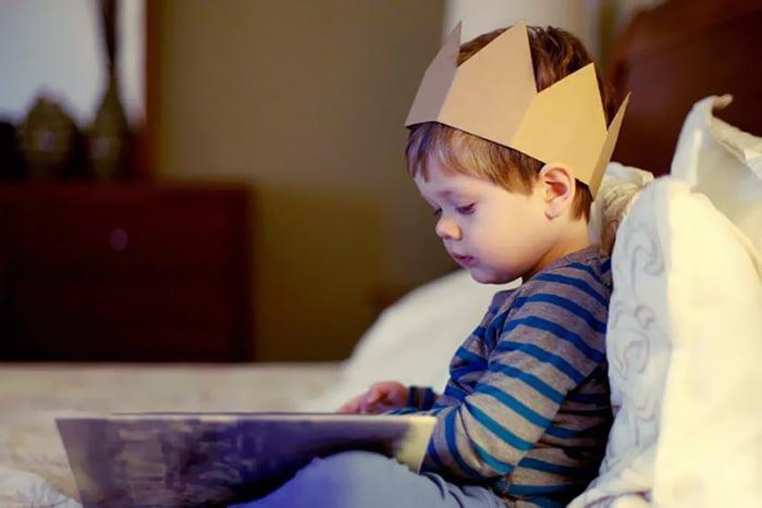 Ребенок в картонной короне читает книжку