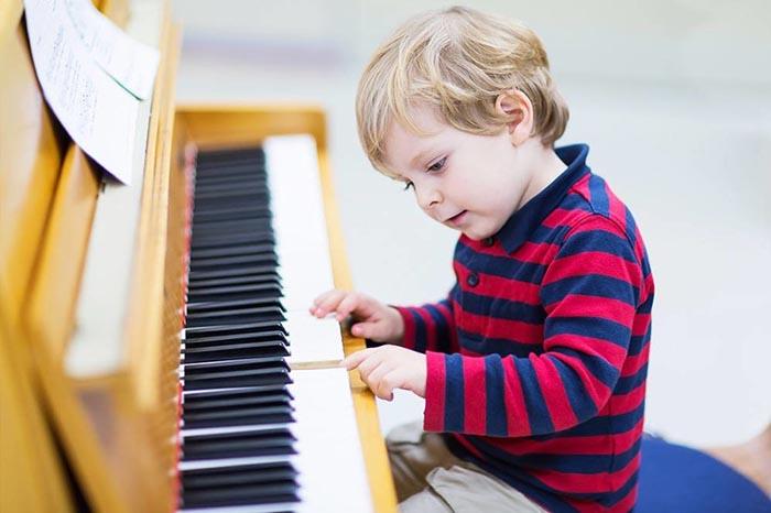 Ребенок учится играть на пианино