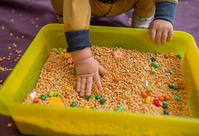 Ребенок играет с коробкой с крупами