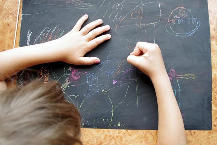 Ребенок выполняет рисунок в технике граттаж