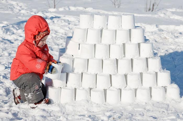 Ребенок строит крепость из снега
