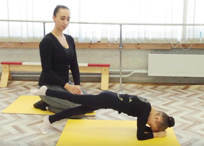 Девочка выполняет упражнение с упором на локти и ногу