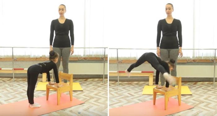 Девочка подпрыгивает, опираясь на стул