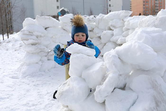 Ребенок строит снежную крепость