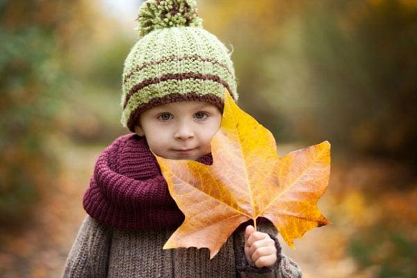 Ребенок с осенним кленовым листом