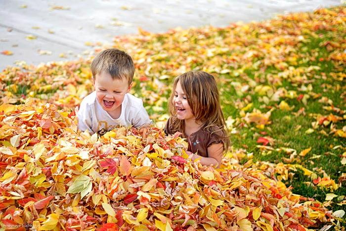 Дети играют в осенних листьях