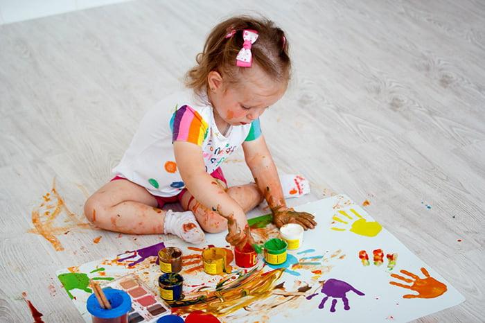 Маленькая девочка рисует пальчиковыми красками
