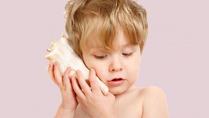Ребенок слушает морскую раковину