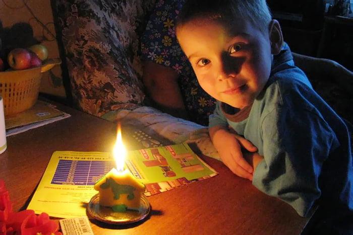 Ребенок за столом со свечой