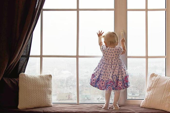 Маленькая девочка держится за ручку окна