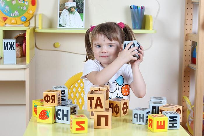 девочка с кубиками для изучения алфавита