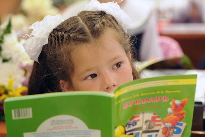 Девочка читает букварь